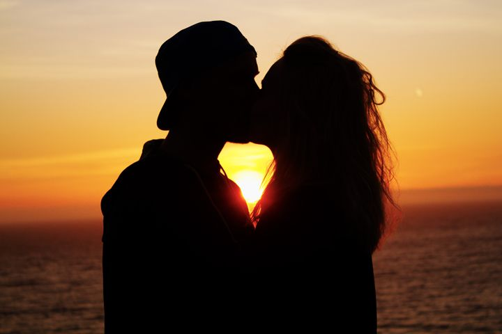 Couple Kissing in front of sunset - Jesse Redheart