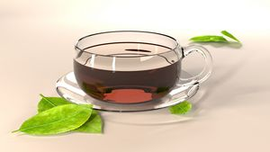 Glass tea cup, saucer and leaves