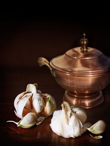 Garlic cloves and an old copper cask