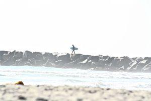 Surfer Walking on Rocks