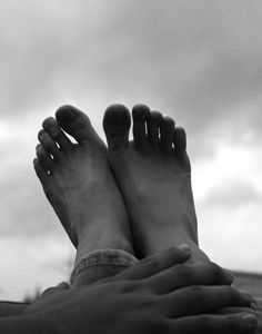 Feet and hand towards clouds