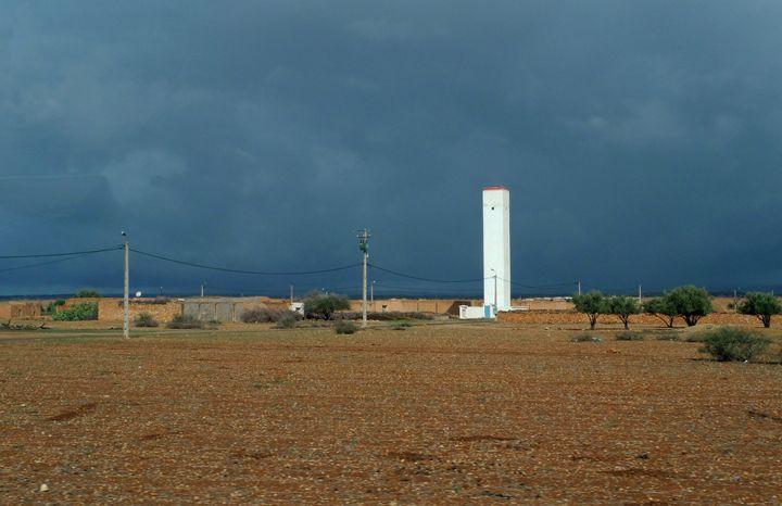 Sunlit tower against storm clouds - John Brooks Art & Photography