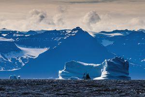 Sailing ship passing glacier, Greenl
