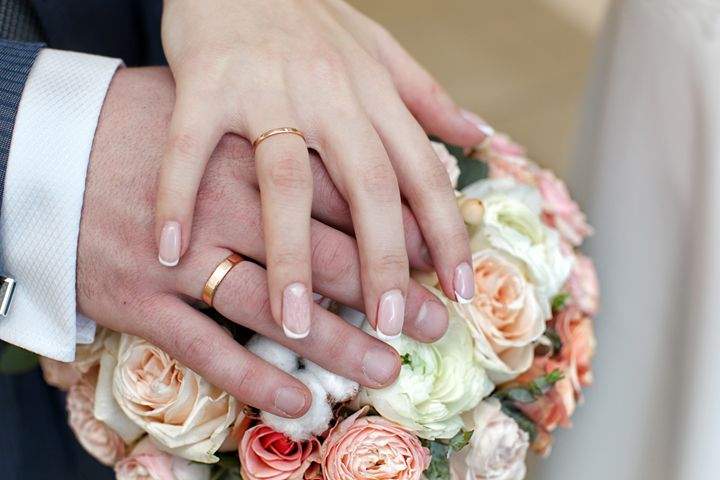 hands of the bride and groom with ri - Radomir