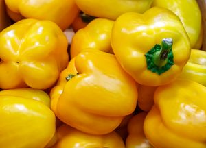 pile of yellow peppers in a box