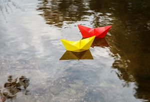 two multicolored paper boats floatin
