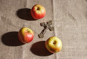 bronze cross and three apples on the