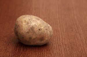 one raw potatoe on the table
