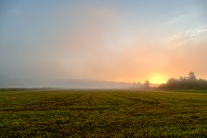 Sunrise in the blue sky in a mist