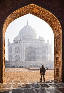 A man looking at the Taj Mahal