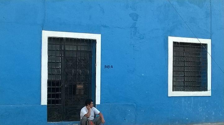 man rests before Merida blue house - bluemeteor