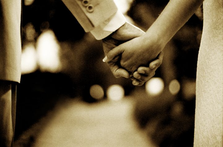 Bride and groom holding hands sepia - edwardolive