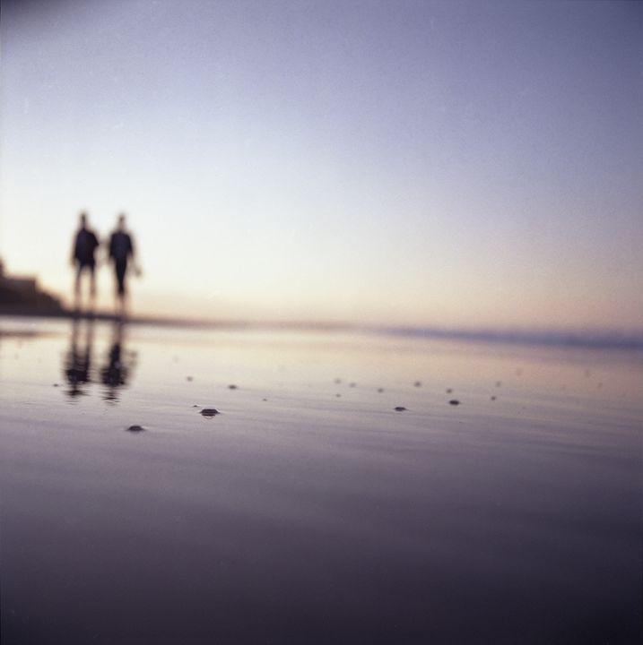 Two people walking on beach summer - edwardolive