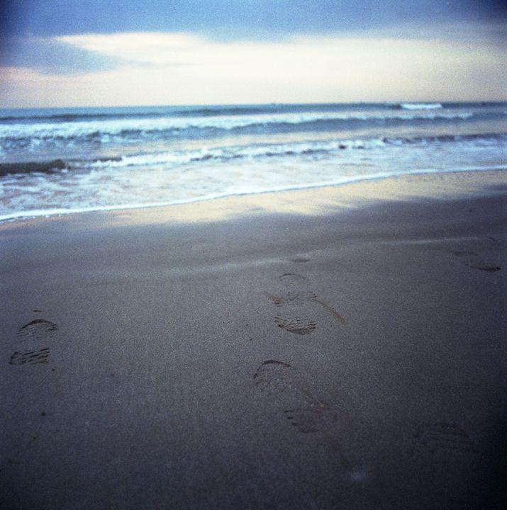 Foot prints at dawn on sandy beach - edwardolive