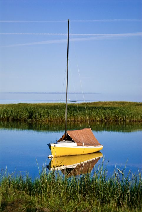Sailboat anchored in salt marsh. - First Light Images