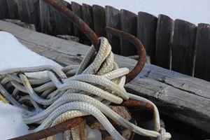 Rusty anchor on weathered wharf