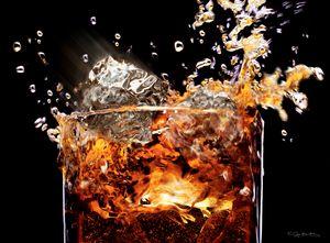 LIQUOR SPLASH ON GLASS AND ICE CUBES