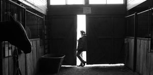 Young Woman Pausing By Barn Door