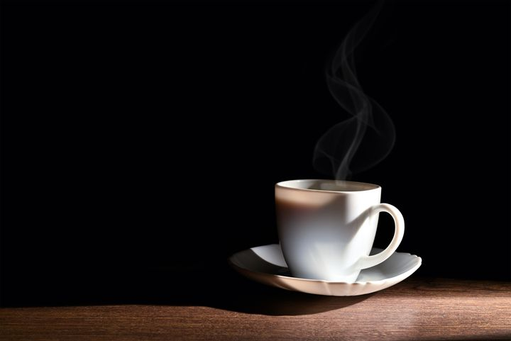 White cup of hot coffee on a dark ba - Dobrydnev