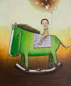 Child rides a green toy horse