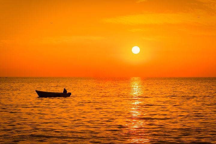 Sea sunset with a fishermans boat si - Tartalja