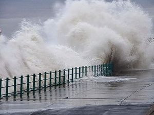 sea water crashing over pier