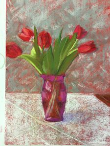 Red tulips in transparent pink vase