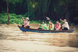 Vietnamese people paddling in a boat