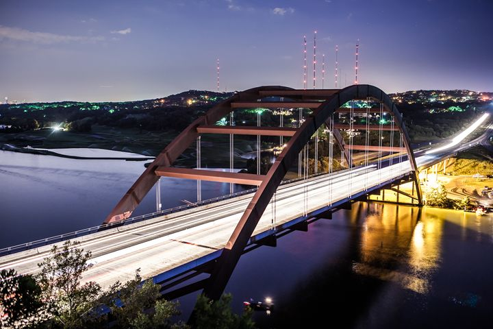 Bridge over water at night - Man On A Roof Productions