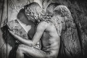 sitting angel reading stone tablet i