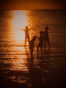 Kids playing in the sunset