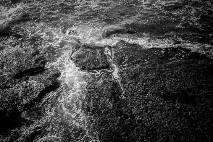 Sea foam and black rocks surface - Maor Winetrob