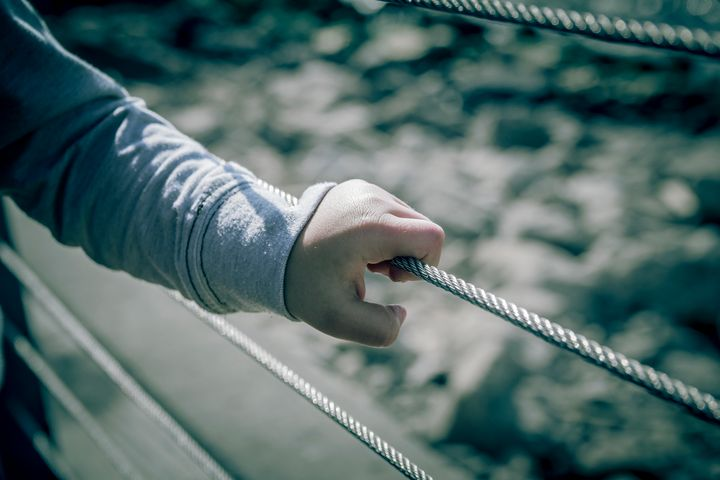 Young boy holding metal wire fence - Maor Winetrob