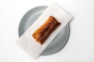 A warm sausage roll on a plate.