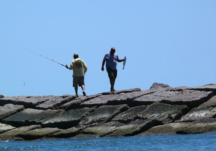 Two men fishing from a jetty in the - Robert Brown Photography