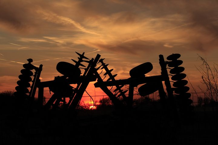 Sunset with farm Equipment and fence - Robert D Brozek